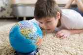Boy studying globe in the room — Foto de Stock