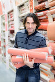 Man holding a roll of wallpaper in the store — Stock Photo
