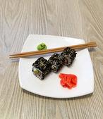 Rollos de sushi, wasabi y jengibre en la placa — Foto de Stock