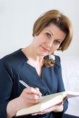 Business woman with book and pen in hand — Stock Photo