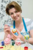 Woman paints the Easter eggs with brush — Stock Photo