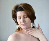 Adult woman with a sore throat on ight background — Stock Photo