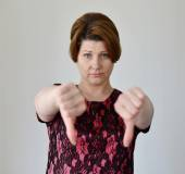 Angry young woman showing thumb down — Stock Photo