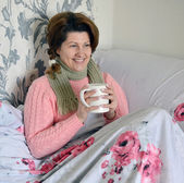 Woman with flu symptoms holding a cup in  hand — Stock Photo