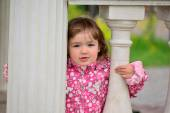 Two year old girl looks out from  gazebo — Stock Photo