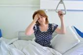 Female patient with headache on bed in hospital ward — Stock Photo