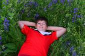 Teenage boy resting on  lawn with blue flowers — Stock Photo