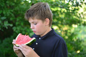 Teen boy eating watermelon in nature — Stock Photo