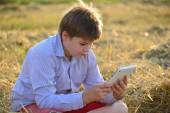 Boy teenager playing on a tablet in the field — Stock Photo