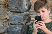 Boy teenager writes sms standing by awooden wall — Stock Photo