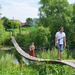 People walk on  suspension bridge over the river — Stock Photo #81166702