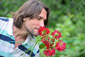 A man near the flowerbeds in the garden — Stock Photo