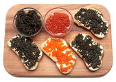 Black and red caviar in glass container — Stock Photo