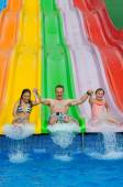 Happy family jump from the slide — Stock Photo