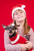 Child girl and dog in Christmas colors — Stock Photo