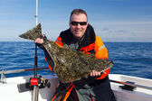 Happy angler with halibut fish — Stock Photo