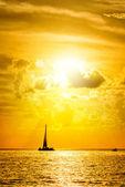 Sailboat and disherman at sunset — Stock Photo