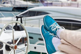 A pair of human legs in pants and bright blue topsiders on yacht — Stock Photo