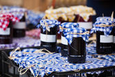 Many preserving jars with dark jam in a market — Stock Photo