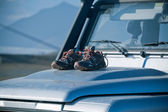 Trekking shoes are drying on a dirty 4wd car bonnet — Stock Photo