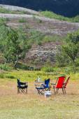 Camping site with camp-chairs and table — Stock Photo