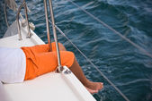 Young boy sitting on a yacht side — Стоковое фото