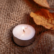 Dry maple leaves and warm candle light — Stock Photo #54874955