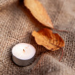 Dry maple leaves and warm candle light — Stock Photo #54875007