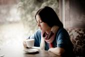Beautiful young woman with a cup of tea at a cafe — Stock Photo