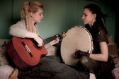 Two beautiful woman with  tambourine and guitar — Stock Photo