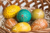 Hand-painted easter eggs in brown basket — Stock Photo