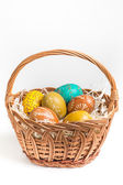 Hand-paited easter eggs in brown basket on white — Stock Photo