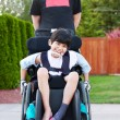 Happy little disabled boy outdoors in wheelchair — Stock Photo #55840521