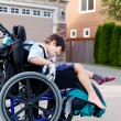 Happy little disabled boy outdoors in wheelchair — Stock Photo #55840529