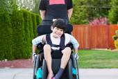 Happy little disabled boy outdoors in wheelchair — Stock Photo