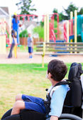 Disabled little boy in wheelchair watching children play on play — Stock Photo