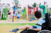 Disabled little boy in wheelchair watching children play on play — Stockfoto