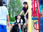Disabled boy in wheelchair enjoying watching friends play at par — Stock Photo