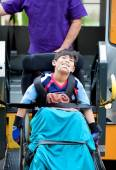 Disabled boy riding on school bus lift — Stock Photo