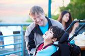 Father talking with disabled son in wheelchair outdoors — Stock Photo