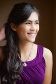 Beautiful biracial young woman in purple dress smiling off to si — ストック写真