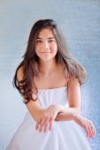 Beautiful biracial teen girl in white dress, sitting arms crosse — Stok fotoğraf