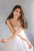 Beautiful biracial teen girl in white dress, sitting arms crosse — Foto Stock