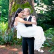 Caucasian groom carrying his biracial bride outdoors, with a kis — Stock Photo #60580783