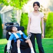 Disabled little boy in wheelchair with sister on grassy lawn out — Stock Photo #60581109