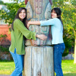 Two young, biracial teen girl in park hugging a totem pole on su — Stock Photo #60581303