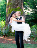 Caucasian groom carrying his biracial bride outdoors, with a kis — Stock Photo