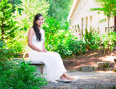 Beautiful biracial bride in white lace wedding dress sitting on  — Стоковое фото