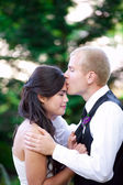 Caucasian groom lovingly kissing his biracial bride on cheek. Di — Stock Photo