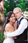 Caucasian groom holding his biracial bride, smiling. Diverse cou — Stock Photo